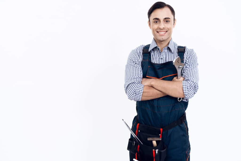 A man of Arab appearance works as a repairman. Handyman posing on white background. A man in uniform holds a adjustable spanner.